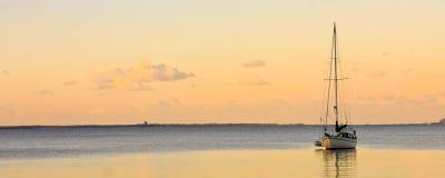 Iate da navigação no mar calmo no por do sol Fotografia de Stock Royalty Free