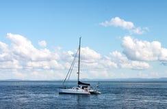 Iate do catamarã no oceano com as montanhas na costa no horizonte sob o céu azul com nuvens imagens de stock
