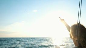 Iate encaracolado novo da navigação da menina que mostra um dedo em um plano que decola no por do sol video estoque