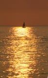 Iate mostrado em silhueta contra um mar dourado. Imagens de Stock Royalty Free
