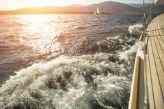 Iate, navegando a regata durante o por do sol imagens de stock royalty free