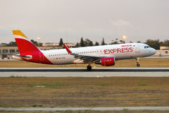 Iberia Express sunset landing. Luqa, Malta - 21 June 2016: Iberia Express Airbus A320 [EC-LYM] arriving well after sunset, wearing the new Iberia Express livery Royalty Free Stock Photography