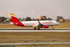 Iberia Express sunset landing. Luqa, Malta - 21 June 2016: Iberia Express Airbus A320 [EC-LYM] arriving well after sunset, wearing the new Iberia Express livery Royalty Free Stock Image
