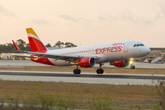 Iberia Express sunset landing. Luqa, Malta - 21 June 2016: Iberia Express Airbus A320 [EC-LYM] arriving well after sunset, wearing the new Iberia Express livery Royalty Free Stock Images