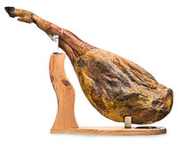Iberian ham isolated. A front leg of Serrano ham mapped on a wooden stand on a white background Royalty Free Stock Image