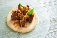 Iberico pig cheeks pork meat with mangetout sugar snap peas Stock Image