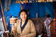 Ibetian woman praying with traditional hand prayer wheel Royalty Free Stock Photos