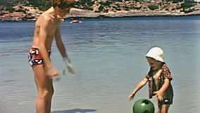 Ibiza children playing. Ibiza, Spain - circa 1973: Restored footage of two funny tourist little boys on holiday playing with a soft ball in the sea of the beach stock video