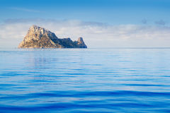 Ibiza Es Vedra island in calm blue water Stock Photos