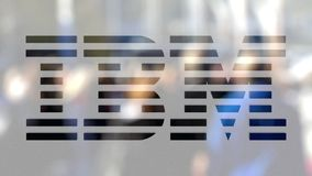 IBM logo on a glass against blurred crowd on the steet. Editorial 3D rendering. IBM logo on a glass against blurred crowd on the steet. Editorial 3D Royalty Free Stock Image
