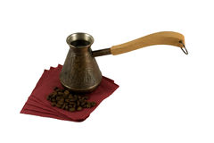 Ibrik with coffee on a serviette with coffee beans. Ibrik with hot prepared coffee on a red serviette with coffee beans Royalty Free Stock Photo