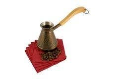 Ibrik mit Kaffee auf einer Serviette mit Kaffeebohnen stockfotografie