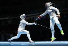 Ibtihaj Muhammad de Estados Unidos R y Sofya Velikaya de Rusia compiten en el equipo del ` s SABRE de las mujeres de la Río 2016  Fotografía de archivo