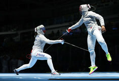 Ibtihaj Muhammad des Etats-Unis R et Sofya Velikaya de la Russie concurrencent dans l'équipe de sabre du ` s de femmes de Rio 201 Photographie stock