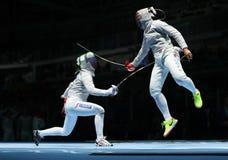 Ibtihaj Muhammad des Etats-Unis R et Sofya Velikaya de la Russie concurrencent dans l'équipe de sabre du ` s de femmes de Rio 201 Photo stock