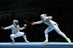 Ibtihaj Muhammad of United States R and Sofya Velikaya of Russia compete in the Women`s Sabre Team of the Rio 2016 Olympic Games Royalty Free Stock Photography