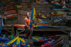 Ibu邪魔是从Ubud的一位工匠 每天她做了被画并且被上色使用明亮和的微型海浪小船工艺 图库摄影