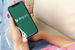 Icône d'application de terril sur le plan rapproché d'écran de l'iPhone X d'Apple chez des mains de la femme Icône des annonces A Photo libre de droits