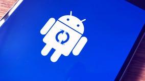 Icône de logo de robot d'Android sur l'écran intelligent de téléphone pendant l'installation de mise à jour banque de vidéos
