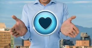 Icône et homme d'affaires d'amour de coeur avec la paume de mains ouverte dans la ville Photos stock