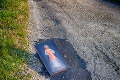 Icône compatissante de Jésus sur la route goudronnée de saleté image stock