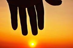 Icône de ciel de coucher du soleil et de main de silhouette Images stock
