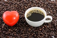 Icône de coeur et tasse de café avec des haricots Photos stock