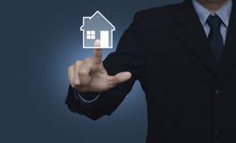 Icône de maison de pressing d'homme d'affaires sur le fond bleu, immobiliers Image libre de droits