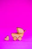 Icône en bois de boguet de bébé et de peu de coeur sur le fond cramoisi Photographie stock