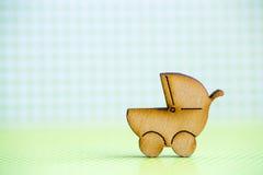 Icône en bois de boguet de bébé sur le fond à carreaux vert Image stock