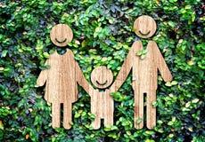 Icône en bois de famille heureuse sur le mur vert de feuille, concept d'Eco Photographie stock
