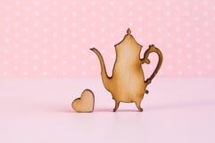 Icône en bois de théière avec peu de coeur sur le fond rose Photographie stock libre de droits