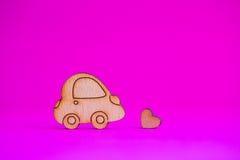 Icône en bois de voiture avec peu de coeur sur le fond cramoisi Image stock