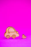 Icône en bois de voiture avec peu de coeur sur le fond cramoisi Photo stock