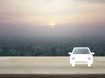 Icône plate de voiture sur la table en bois au-dessus de la vue aérienne du paysage urbain Photo stock