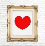 Icône rouge de coeur dans le cadre d'or de photo de vintage sur le mur de briques blanc Photo stock