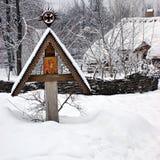 Icône sur la croix en bois sous la neige Photographie stock