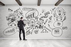 Icônes d'homme d'affaires et de démarrage sur le mur en béton Photo stock