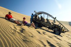 ICA, PERU - JULY 6, 2010: Sand dune buggy parked on a dune and group of people having fun. Ica, Peru.  stock image