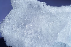 Ice. Piece of frosted melting ice on blue background Royalty Free Stock Photo
