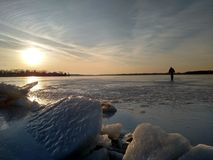 Ice meets Sky. Beginning the adventure. Crystal clear frozen lake during sunset on Cass Lake in Keego Harbor, Michigan. January 15, 2017. Model Unknown Stock Photo