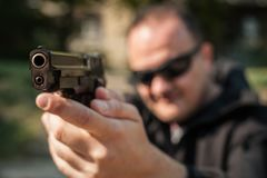 Police agent and bodyguard pointing pistol to protect from attacker stock photography