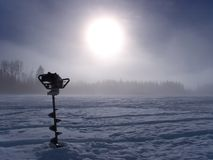 Ice Auger. An ice auger driven into the ice on a foggy winter's morning royalty free stock images
