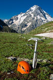 Ice-axe and helmet on the mountain background. Stock Photos