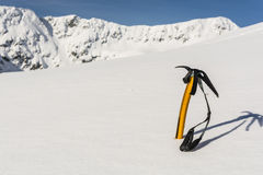 Ice axe stuck in the snow on the slopes. Stock Images