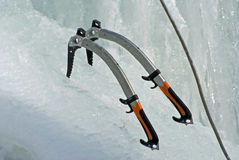 Ice Axes. A pair of ice axes and a climbing rope at the bottom of an ice cliff Stock Photo