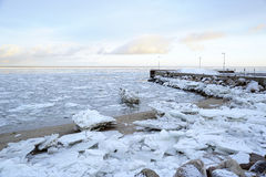 Ice on the beach and quay. Big chunk of ice at a sand beach on a winter day, near a quay Royalty Free Stock Photos