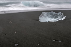 Ice berg at sea shore. Ice berg alone black diamond beach shore washed away by waves, Iceland Stock Image
