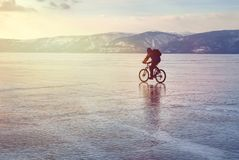 Ice biker traveler with backpacks on bike on ice of Lake Baikal. Against the background of sunset sky, ice surface. Winter sport Stock Image