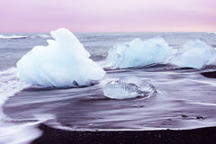 Ice on the black beach of Jokulsarlon, Iceland. Ice on the black beach with the slow flow of wave at Jokulsarlon, Iceland Royalty Free Stock Image